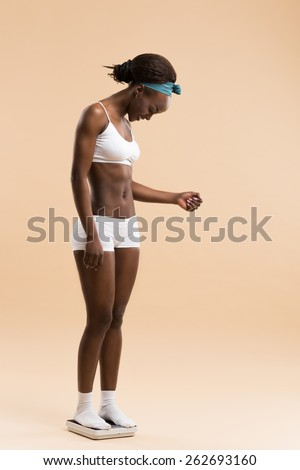 African woman standing on scale celebrating weightloss and a healthy fit body - stock photo