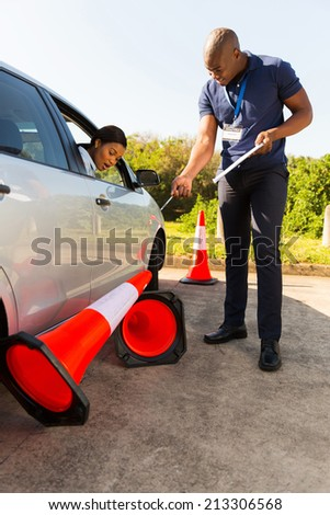 african woman taking driving lessons and running over traffic cone - stock photo