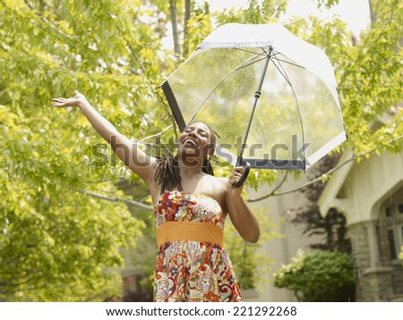 African woman with arm outstretched under umbrella