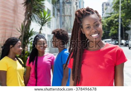 African woman with dreadlocks and girlfriends in the city - stock photo