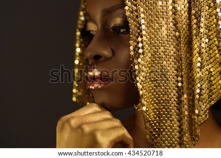 African woman with gold metallic make-up and full shiny lips looking away holding chin, close up - stock photo