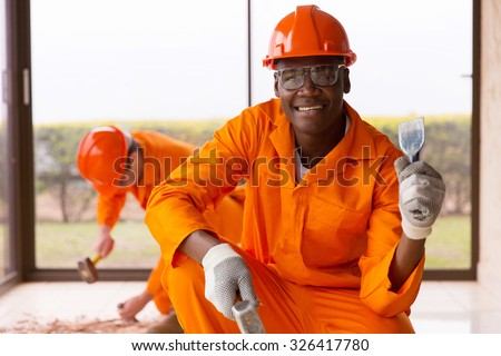 african workman holding chisel and hammer inside house under construction - stock photo