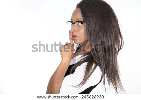 African young girl covering her mouth with finger be quiet - stock photo