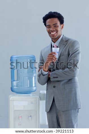 Afro-American businessman drinking from a water cooler in office - stock photo