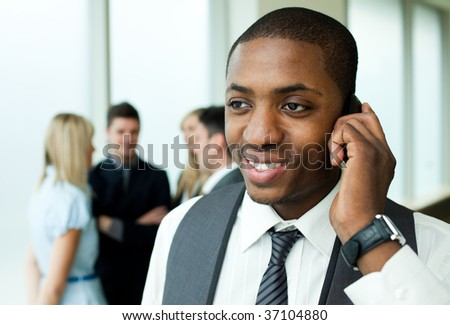 Afro-American businessman on phone in office with his team in the background