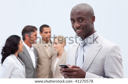 Afro-American businessman sending a text in front of his team