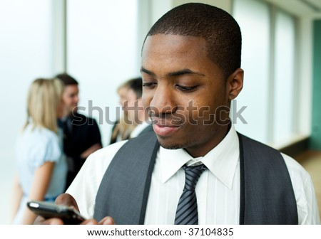 Afro-American businessman sending a text in office