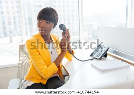 Afro american businesswoman covering microphone on phone and looking away in office - stock photo