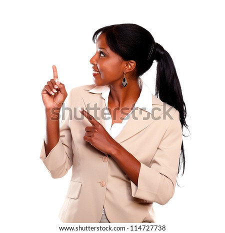 Afro-american businesswoman pointing up against white background - stock photo