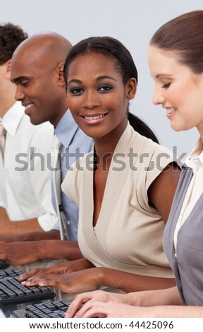 Afro-american businesswoman sitting in a line with her colleagues smiling at the camera