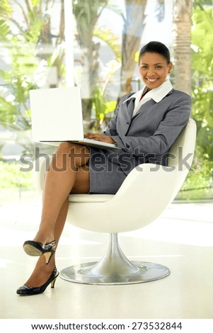 Afro American businesswoman using laptop on knees - stock photo