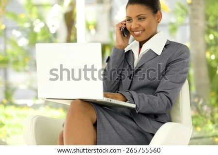 Afro American Businesswoman using laptop on knees and giving a phone call with cell phone - stock photo