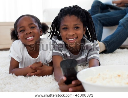 Afro american children watching television and eating pop corn in the living room - stock photo