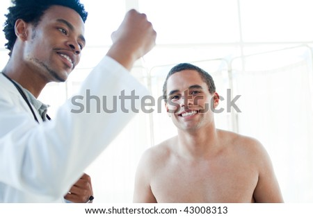 Afro-american doctor checking patient's temperature in a hospital - stock photo