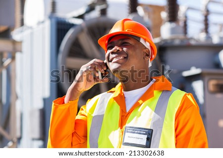 afro american electrical engineer talking on smart phone in electricity power plant - stock photo