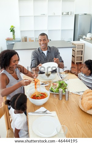 Afro-american family dining together in the kitchen - stock photo
