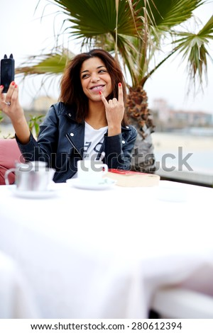 Afro american female taking fun self portrait with smart phone camera while sitting at cafe terrace near the beach, hipster young woman taking a picture of herself on her cell phone looking playful  - stock photo