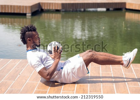 Afro-American man doing exercises for his abs with soccer ball - stock photo