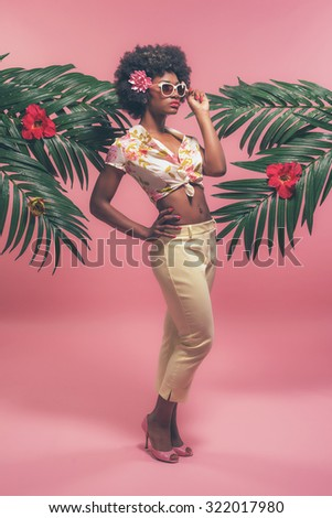 Afro American Pin-up with Sunglasses Between Palm Leaves. Against Pink Background. - stock photo