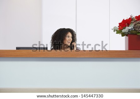Afro American receptionist talking on telephone behind reception desk  - stock photo