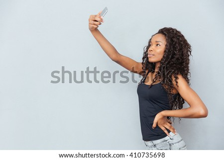 Afro american woman making selfie photo on smartphone over gray background - stock photo