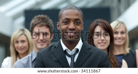 Afro-American young businessman smiling at the camera with his team - stock photo