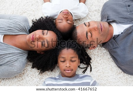 Afro-American young family lying on floor with their heads together - stock photo