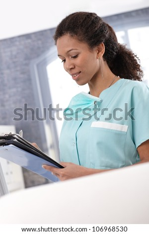 Afro-american young nurse working with case sheets, writing notes. - stock photo