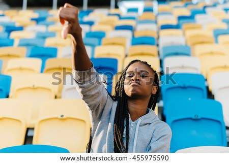 Afro-American young woman doing a thumbs down signal with her hand against stadium rows of seats