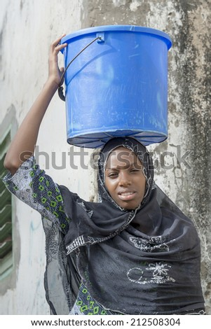 Afro beauty carrying a bucket of water in a slug  - stock photo