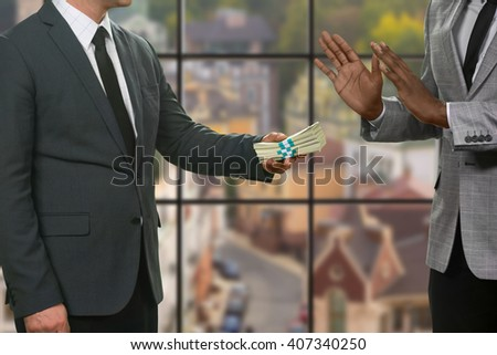Afro businessman refuses money. Men's bribery on urban background. My word doesn't sell. Honesty and courage. - stock photo