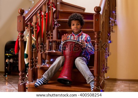 Afro child plays on drum. Kid with drum on Christmas. Young percussion talent. Call it his first concert. - stock photo