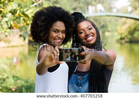 Afro friends having fun in the park taking selfie - stock photo