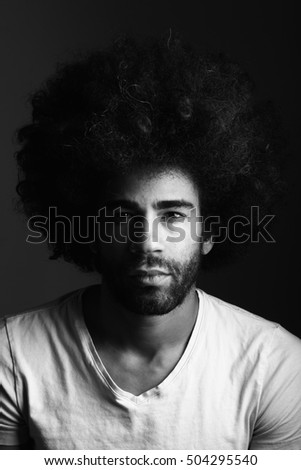 Afro man in front of a dark background