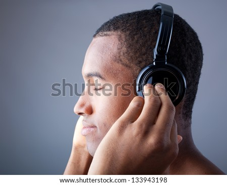 Afro man listening to music on DJ headphones with eyes closed - stock photo