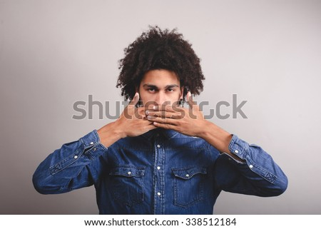 Afro man shut his mouth with his hands. On a gray background. - stock photo