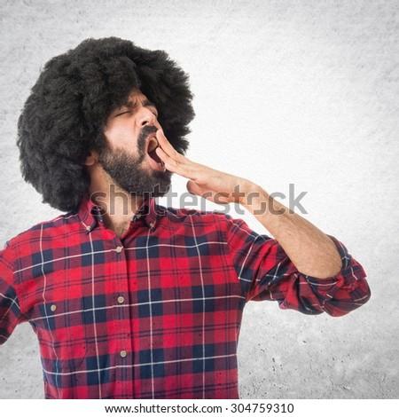 Afro man yawning over grey background - stock photo
