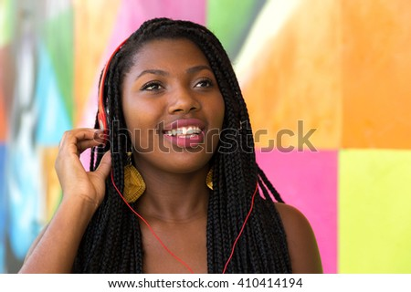 Afro woman listing to music on colorful background - stock photo