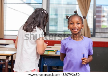 Afroamerican and asian girl in primary school. - stock photo