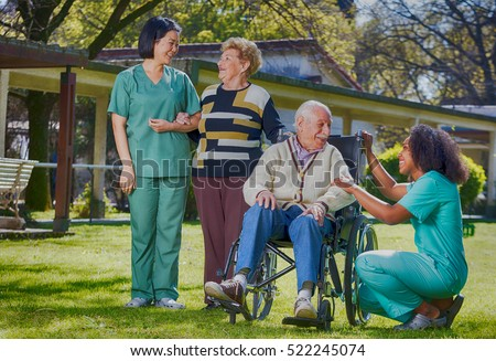 Afroamerican and asian nurses joking with elder people in hospital garden.