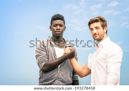 Afroamerican and caucasian men shaking hands in a modern handshake to show each other friendship and respect - Arm wrestling against racism on a blue sky - stock photo
