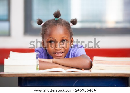 Afroamerican elementary student happy with books on her desk. - stock photo