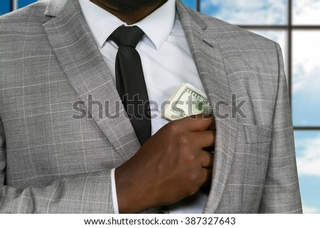 Afroamerican office manager hides money. Black office worker hiding cash. Feed the greed. It's safer to hide.