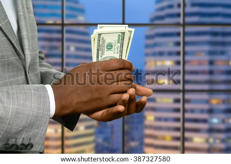 Afroamerican office manager holding salary. Megalopolis businessman holds money. Warm up your pocket. Fresh and crispy. - stock photo