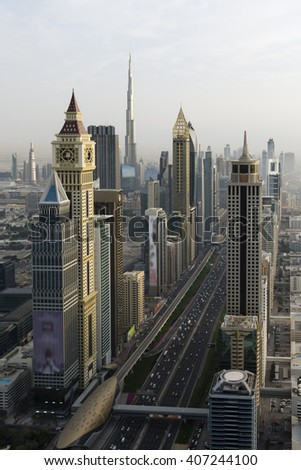 After a day of poor visibility, the sky cleared in the afternoon to provide a beautiful sunset over Dubai. The view looks past the DIFC and Burj Khalifa towards the Burj Al Arab and Dubai Marina. - stock photo