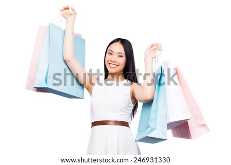 After a day shopping. Beautiful young Asian woman in pretty dress looking at camera and holding shopping bags while standing against white background   - stock photo