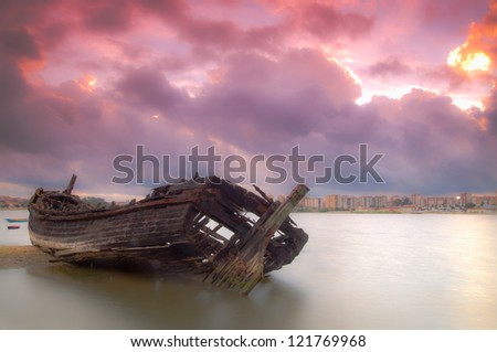 After a long period of time the old boat rests on the river bank - stock photo
