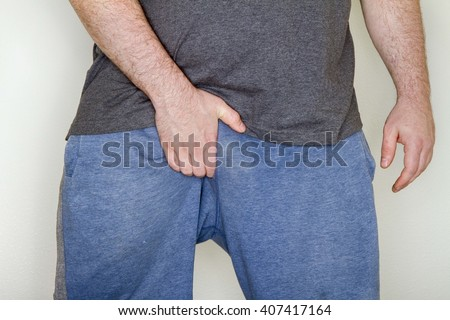 After a long workout a man is scratching his groin due to jock itch - stock photo