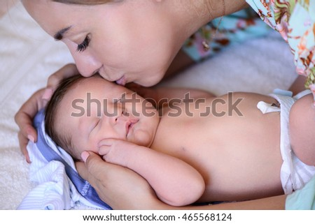 After childbirth newborn baby sleeping in a bed with mammy kiss