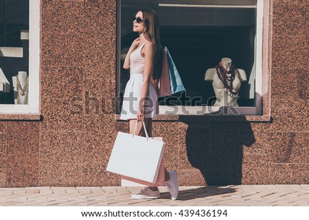 After day shopping. Side view of beautiful young woman carrying shopping bags and smiling while walking along the street with fashion store in the background - stock photo